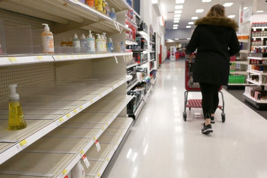 FILE - In this March 3, 2020 file photo, shelves that held hand sanitizer and hand soap are mostly empty at a Target in Jersey City, N.J.    People who may have been exposed to the new coronavirus or who get sick with COVID-19 may be advised to stay home for as long as 14 days to keep from spreading it to others, according to the Centers for Disease Control. That's led many people to wonder if they could manage for two weeks at home without a run to the grocery store.   (AP Photo/Seth Wenig)