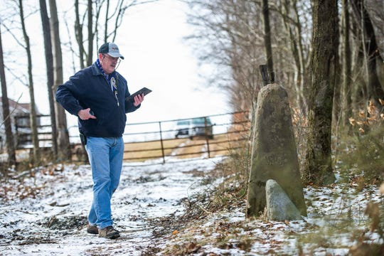 Pat Simon, a land surveyor from Bel Air, Md., and the chief of surveys for Baltimore County, takes a photograph of a concrete state line marker Saturday, Feb. 15, 2020 near the where the borders of West Virginia, Maryland and Pennsylvania converge. Simon was conducting a re-survey of the state lines on Saturday.