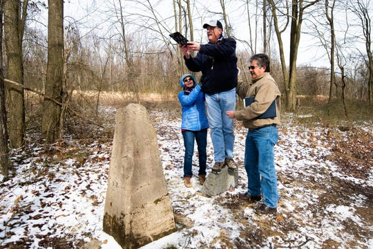 Pat Simon, a land surveyor from Bel Air, Md., and the chief of surveys for Baltimore County, gets balancing help from his wife, Deborah Simon, left, and fellow surveyor Rich Casteel, right, of Clarksburg, W. Va., while the group documents a concrete state line marker, Saturday, Feb. 15, 2020 near the where the borders of West Virginia, Maryland and Pennsylvania converge. Simon was conducting a re-survey of the state lines on Saturday.
