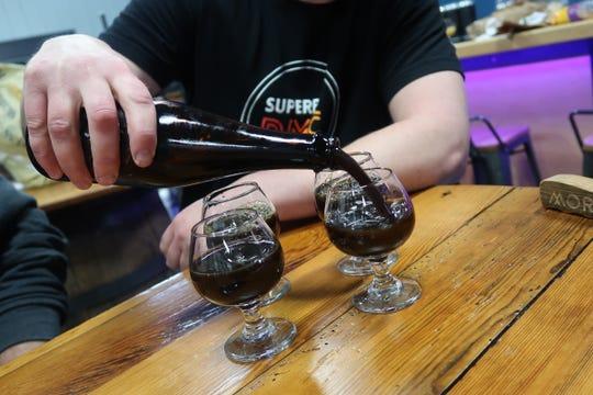 Josh Bauerlein pours samples of Mortalis Brewing's Hazel, a hazelnut coffee imperial stout.