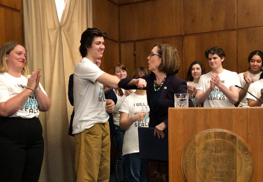 Oregon Gov. Kate brown elbow-bumps student Charlie Abrams at a ceremony on March 10, 2020, where she signed a sweeping executive order for the state to reduce carbon emissions to combat global warming. Amid a spreading coronavirus outbreak, many people are no longer shaking hands and are coming up with alternatives, like the elbow bump.