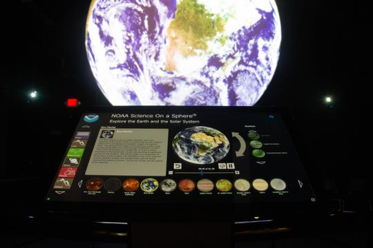 The NOAA Science on a Sphere exhibit offers visitors a chance to explore the earth and solar system.