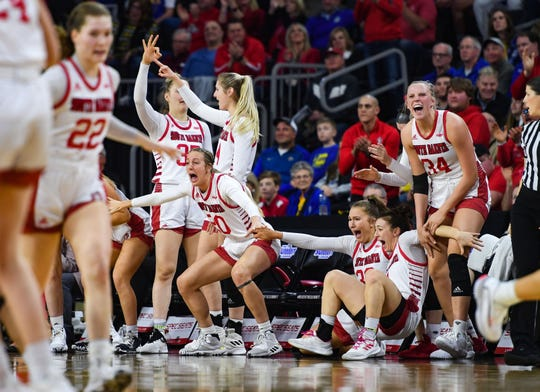 USD teammates react excitedly about a three-point shot that sent the team into the lead in the final quarter of the Summit League championship game on Tuesday, March 10, at the Denny Sanford Premier Center in Sioux Falls.