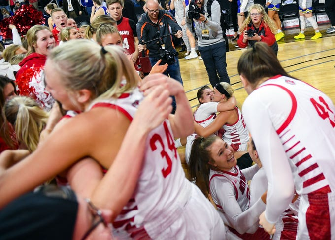 USD players hug and help each other off the floor after falling over while celebrating their Summit League championship win on Tuesday, March 10, at the Denny Sanford Premier Center in Sioux Falls.