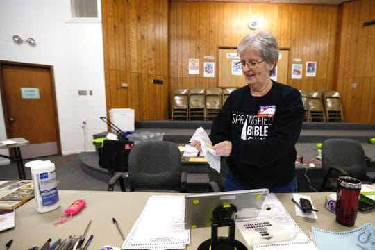 An election judge sanitizes a work area during Tuesday's primary election.