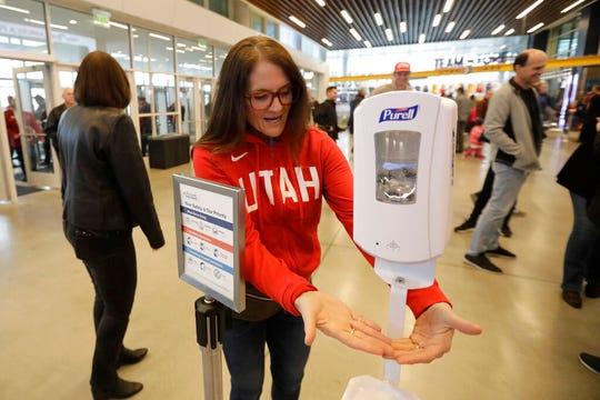 A fan uses a sanitizing station at the Vivint Smart Home Arena before an NBA basketball game between the Toronto Raptors and the Utah Jazz, Monday, March 9, 2020, in Salt Lake City. (AP Photo/Rick Bowmer)