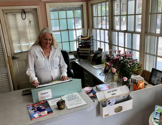Mary Jane Moreton, manager of the Islander Inn in Vero Beach, stands behind her availability logbook Tuesday, March 10, 2020. Moreton has already seen thousands of dollars in losses since initial news broke about positive coronavirus cases on Florida's west coast.