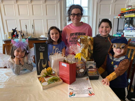 Tamar Weinberg and her children with a Purim package that was delivered to their New Rochelle home. The family has been quarantined since March 4.