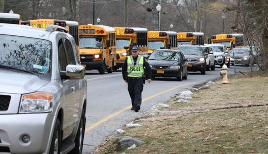 School busses line up in front of New Rochelle High School, as students get ready for dismissal, March 10, 2020.