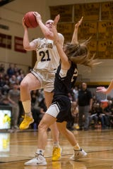 Sanford's Allie Kubek (21) rises above Padua's Skylar Salvo (2) to shoot Monday night in the DIAA girls quarterfinals. Sanford defeated Padua 74-46.