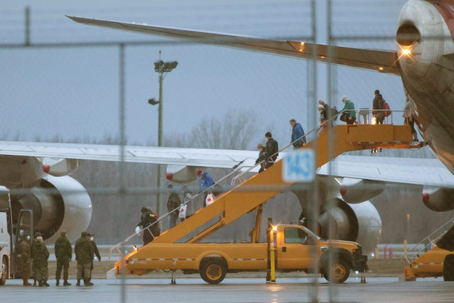 Canadian passengers from the Grand Princess cruise ship step off their repatriation flight from Oakland, California on Tuesday. They will enter quarantine at Canadian Forces Base Trenton in Trenton, Ontario.
