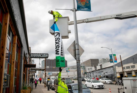 David Rodriguez, top, and Joseph Alberts, of the City of Austin Transportation Department, take down a South by Southwest street banner on East 7th Street outside the music venue Barracuda on Tuesday March 10, 2020, after SXSW was canceled due to the coronavirus scare.