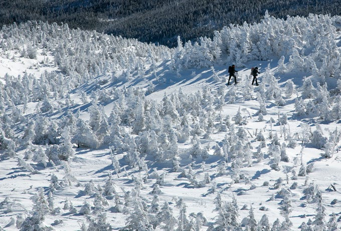 In this Saturday, March 7, 2020 photo, a pair of hikers snowshoe through a forest of rime ice-covered spruce trees on the eastern slope of Mt. Marcy, New York's tallest mountain, near Keene, N.Y. While spring-like weather has been moving into the lower elevations, winter still has the High Peaks region of Adirondack Park firmly in it's grip.