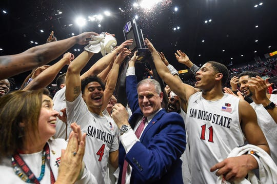 San Diego State head coach Brian Dutcher, center, and players hold up the Mountain West Championship trophy.
