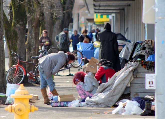 Homeless people crowd a sidewalk in downtown Salem, Ore., where they have set up a makeshift camp. Experts say that the homeless, who often have health and substance-abuse problems, are exposed to the elements and do not have easy access to hygiene, are more vulnerable to the coronavirus.