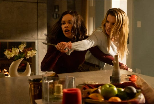 "Athena (Hilary Swank, left) tussles with Crystal (Betty Gilpin) in ""The Hunt."""