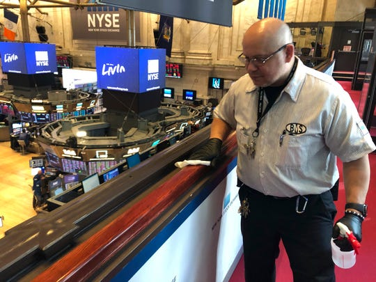 Porter Raul Rodriguez disinfects a railing at the New York Stock Exchange on Monday amid coronavirus fears.