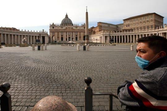 Um hombre porta una mascarilla mientras observa una vacía Plaza de San Pedro, en Italia.