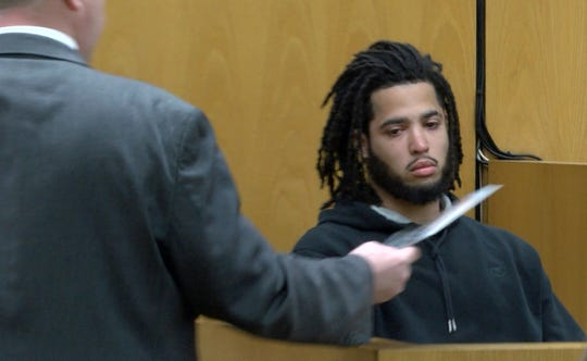 Witness Keon Cooper looks at a photo as he testifies during the murder trial for Anthony Barksdale, aka Shakar Barksdale, in State Superior Court in Toms River Wednesday, March 11, 2020.  He discovered Steven Stallworth's body outside his apartment door and made a 911 call to police.