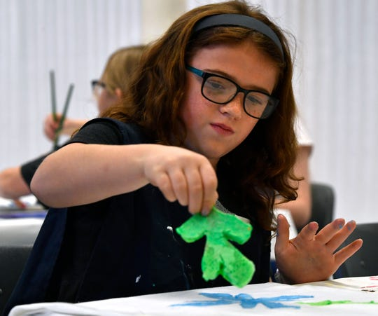 Grace Thompson, 10, uses a sponge to create a Matisse-themed T-shirt Wednesday at the Grace Museum.