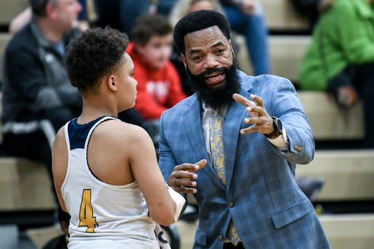 Battle Creek Central's head coach Tony Warren, right, talks with Jadaneic Williams during the first quarter on Tuesday, March 10, 2020, at Holt High School.