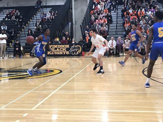 Children's Village's Dezmound Singleton dribbles as Marathon's Joseph Hurlbert defends during Tuesday's Class D state first-round playoff game at Windsor High. Marathon won, 61-33.