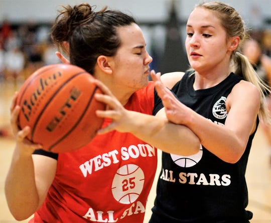 North Mason's Natalie Carstensen (right) defends Klahowya's Sarah Greene during Tuesday's West Sound Senior High School All-Star Basketball Games gathering at Olympic College.
