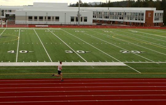 A lone runner does laps at the empty athletic complex at Central Kitsap High after school on Wednesday, March 11, 2020.