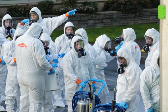 Workers from a Servpro disaster recovery team wearing protective suits and respirators enter the Life Care Center in Kirkland, Wash., to begin cleaning and disinfecting the facility, Wednesday, March 11, 2020, near Seattle. The nursing home is at the center of the coronavirus outbreak in Washington state. For most people, the virus causes only mild or moderate symptoms. For some it can cause more severe illness, especially in older adults and people with existing health problems.