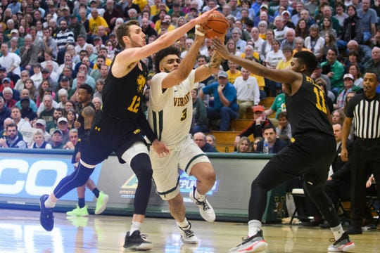 Vermont's Anthony Lamb (3) drives to the hoop past UMBC's Brandon Horvath (12) and R.J. Eytle-Rock (11) during the America East men's basketball semifinal game between the UMBC Retrievers and the Vermont Catamounts at Patrick Gym on Tuesday night March 10, 2020 in Burlington, Vermont.