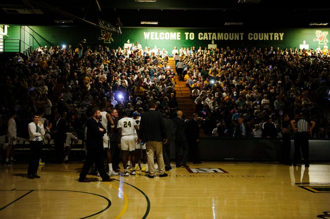 Fans hold up cell phone flashlights as the power goes out during the America East men's basketball semifinal game between the UMBC Retrievers and the Vermont Catamounts at Patrick Gym on Tuesday night March 10, 2020 in Burlington, Vermont.