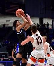 Logan Woods (left) of Cincinnati Christian lands a jumper for a basket for the Cougars at the OHSAA Division IV regional semifinal March 10, 2020.