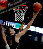 Moeller High School forward Logan Duncomb gets the basket and the foul from Centerville forward Mo Njie during their Division I regional semifinal boys basketball game at the Cintas Center in Cincinnati Wednesday, Mar. 11, 2020.