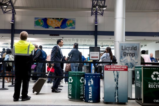 Travelers wait in the security line at Cincinnati/Northern Kentucky International Airport in Hebron, Ky., on Wednesday, March 11, 2020.