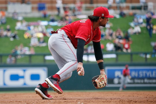 Cincinnati Reds third baseman Alex Blandino looks to throw to first base on an infield single hit by Colorado Rockies' Trevor Story during the third inning of a spring training baseball game Tuesday, March 10, 2020, in Scottsdale, Ariz.