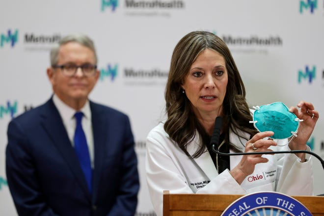 Ohio Department of Health Director Amy Acton holds up a mask as she gives an update at MetroHealth Medical Center Thursday, Feb. 27, 2020, in Cleveland. Ohio Governor Mike DeWine, left, watches.