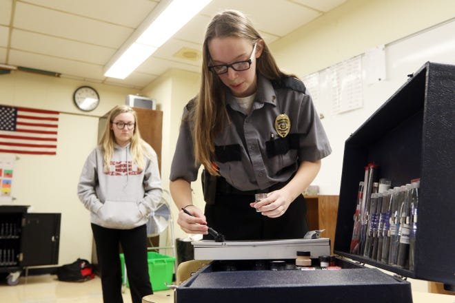 Coshocton County Career Center criminal justice major Diana Freitag takes seventh-grader Danielle Hill's fingerprints off a clipboard during career day presentations at Coshocton Middle School.