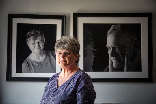 Margo Ryan stands in her bedroom with portraits of her and her husband, Ron, who is in hospice at the Sunny View Care Center in Ankeny. Margo is no longer able to visit her husband because the center is locked down due to concerns about coronavirus.
