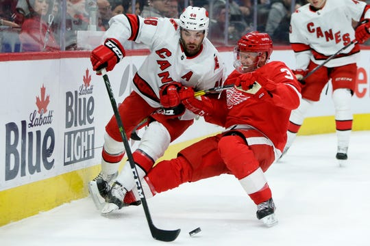 Carolina Hurricanes left wing Jordan Martinook is pulled to the ice by Detroit Red Wings defenseman Alex Biega during the first period Tuesday, March 10, 2020, in Detroit.