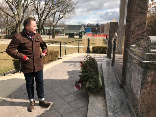 David London, a veteran who is chair of the city's Veterans Event Committee, looks over the names  of military dead on the Royal Oak war memorial on March 4. The memorial is planned to move 40 feet to London's left.