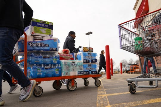 People grab supplies while shopping at Costco in Auburn Hills on Wednesday, March 11, 2020.