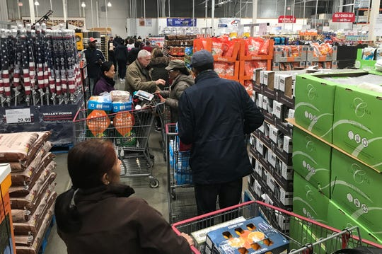 A day after the first two cases of coronavirus were reported in Michigan, shopping lines are long and shopping carts are full at the Costco in Madison Heights.