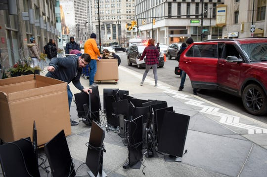 Quicken Loans employee Kyle Navarre sorts through computer monitors as the company distributes computers and other office supplies to employees in front of the Chrysler Building on Fort Street.