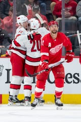 Detroit center Luke Glendening looks away as Carolina celebrates a goal by right wing Justin Williams in the third period.