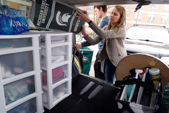Jenni Phillips of Brownstown helps her son, Michigan State University freshman Jacob Phillips, load his belongings into the family van as he moves out of East Akers Residence Hall on MSU's campus in East Lansing Wednesday, March 11, 2020