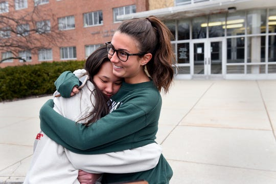Michigan State freshmen Julia Blumbergs of Beverly Hills, Mich., left, and Gabby Peruski of Grosse Pointe hug as they move their belongings out of South Wonders Residence Hall on the MSU campus in East Lansing March 11.