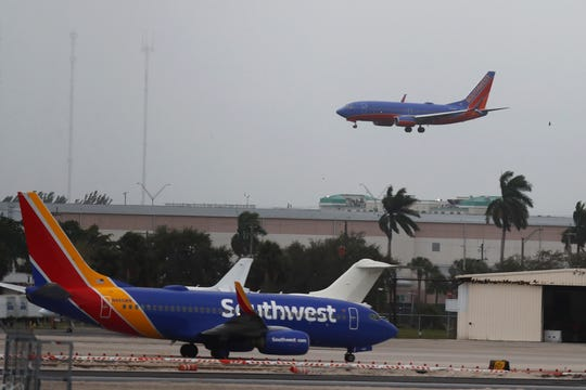 FILE - In this Jan. 10, 2020 file photo, a commercial plane flies into a windy, cloudy sky at the Fort Lauderdale-Hollywood International Airport in Fort Lauderdale, Fla.