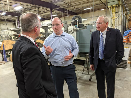 Tom Conrad, center, of Crescent Manufacturing, speaks with Ohio Treasurer Robert Sprague, left, and 88th House District Rep. Bill Reineke, right during a tour of the Fremont facility.