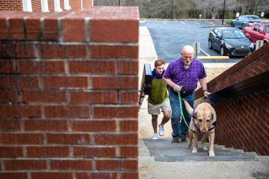 """Robert """"Skeeter"""" Powell, founder of David's Table, a nonprofit providing resources for teens and young adults with disabilities, walks his therapy dog Chief during a Monday Club session at Rocky Creek Baptist Church Monday, March 9, 2020."""