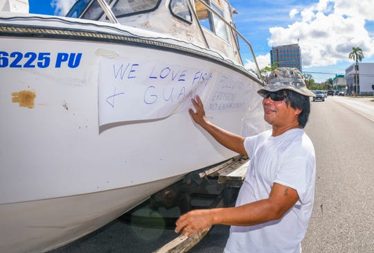Fisherman Jonathan Deloso prepares to add another sign his boat, which was being used to display a collection of signs expressing his opposition of Bill 53 outside the Guam Congress Building in Hagåtña on Wednesday, March 11, 2020. Bill 53 would prohibit fishing in the waters off Guam while using scuba or similar equipment.